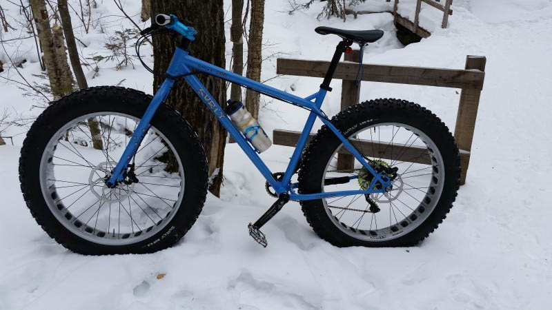 Left side view of a blue Surly fat bike, parked in the snow, leaning on a tree