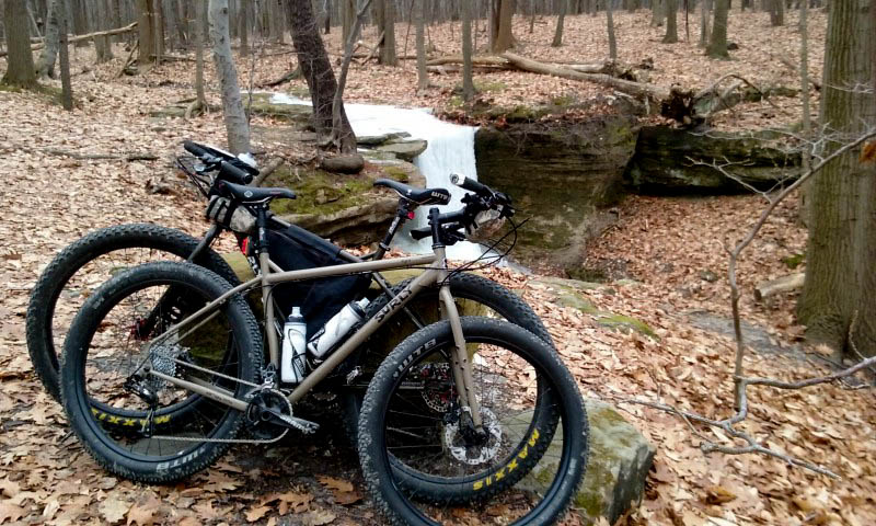 Side view of 2 Surly bikes leaning against each other, on a large rock in the woods, with a stream in the background