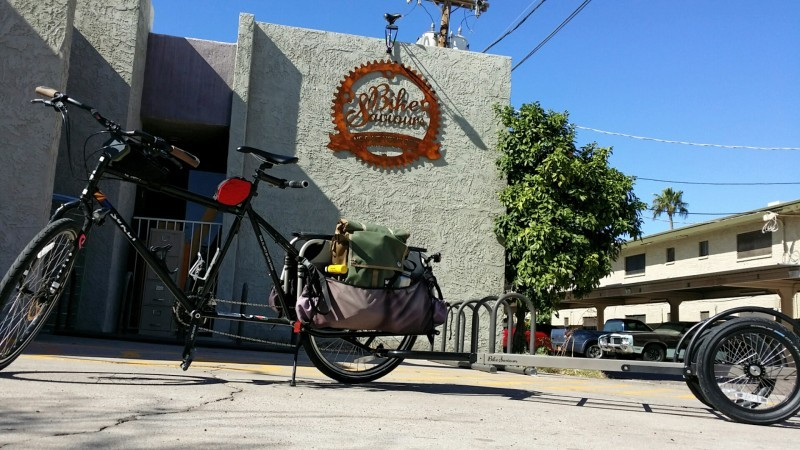 Left side view of a black Surly Big Dummy bike with a trailer, parked in front of a bike shop