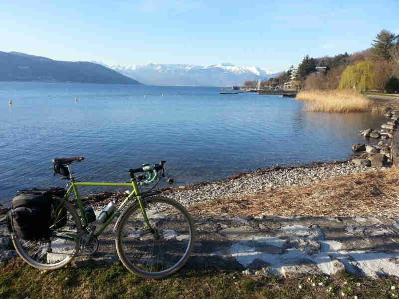 Right side view of a green Surly Cross Check bike, parked on a lakeshore, with mountains in the background