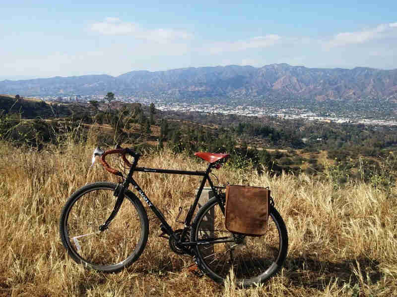 Left side view of a black Surly Cross Check bike parked in grass on a hilltop, with mountains in the background
