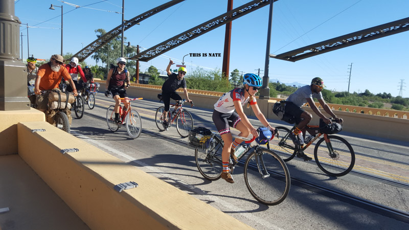 Front left side view of a group of cyclists riding on a bridge, with an arrow pointing at a person named Nate