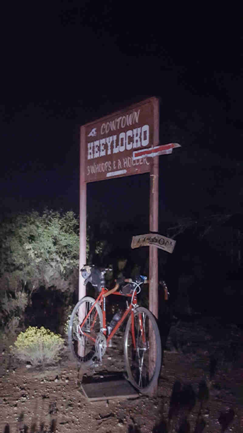 Front right side view of a Surly bike parked next to a Cowtown Heeylocko sign, in the dark