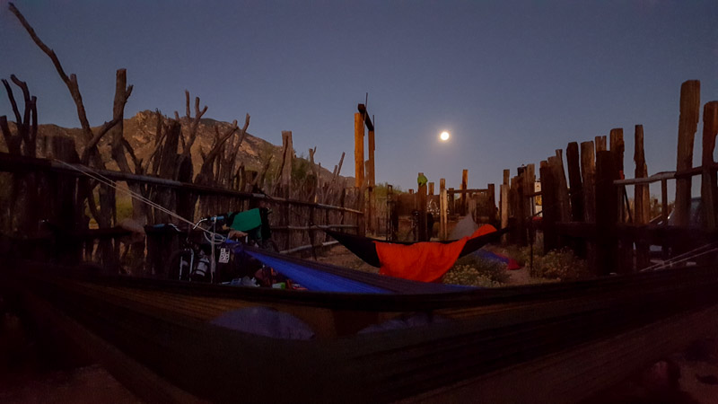 Hammocks hanging inside of a wood corral, with hills and the moon in the background