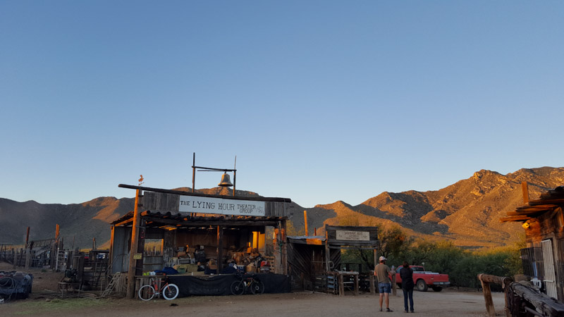 Front view of the outside of a wooden desert theater building, with hills in the background