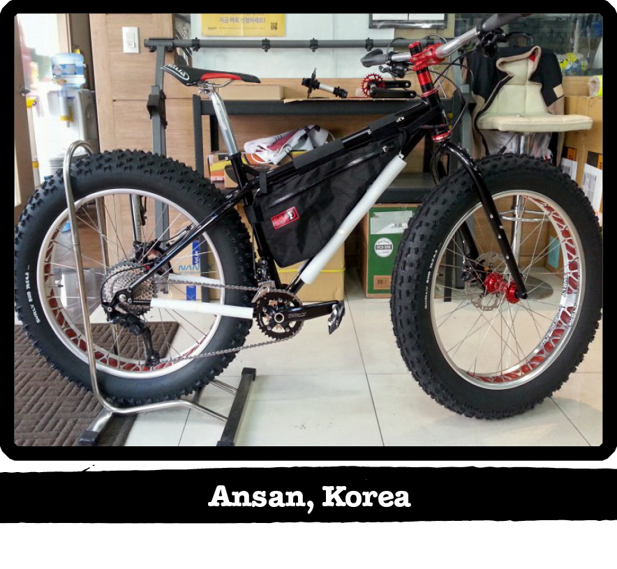 Right profile of a Surly fat bike with the back tire in a stand on an office floor-Ansan, Korea banner shown below image