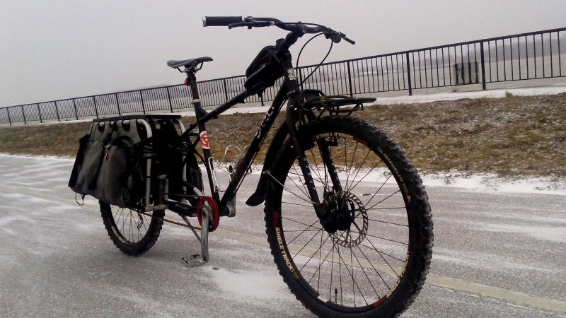Front right side view of a black, Surly Troll bike, in the middle of an icy road, with a fence in the background