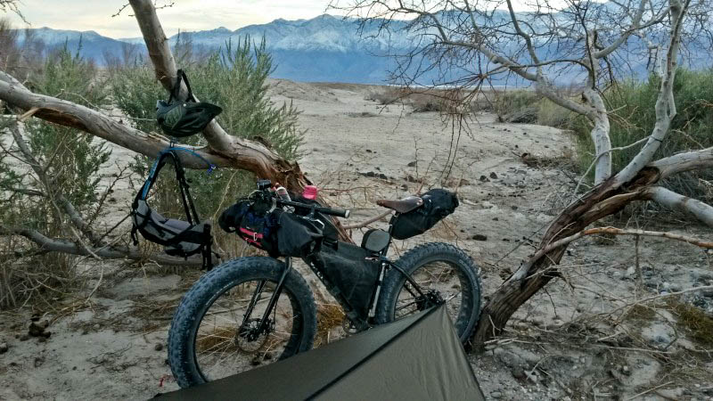 Left side view of a Surly fat bike standing in a sandy field, in front of a small tree, with mountains in the background