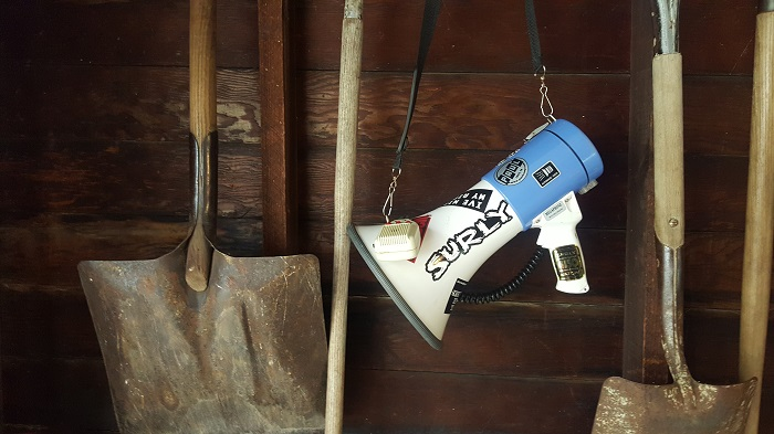 A blue and white megaphone with a Surly sticker on it, hanging down in front of a wood barn wall with shovels on it