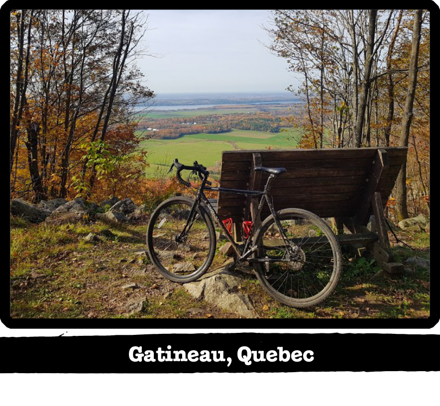 Left profile of a Surly bike leaning on a park bench overlooking a green valley-Gatineau, Quebec banner under image