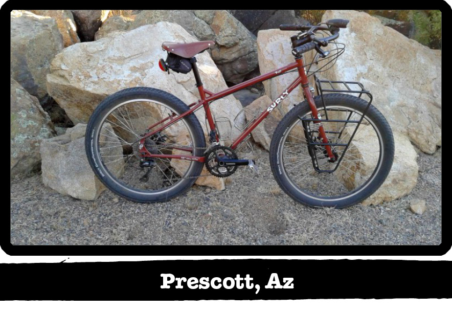 Right side view of a dark red Surly bike in front of boulders-Prescott, AZ banner below image
