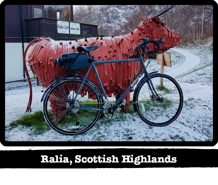 Right profile of a Surly bike in the now in front of a red cow statue- Ralia, Scottish Highlands banner below image
