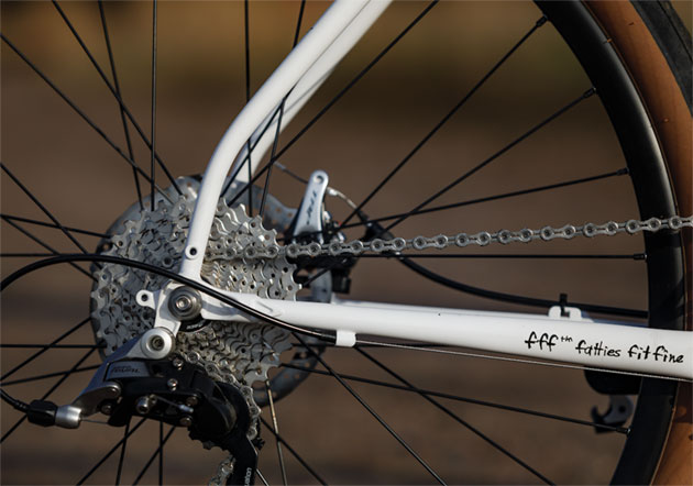 Zoomed in right side view of the rear axle plate, cassette and derailleur of a white Surly Midnight Special bike
