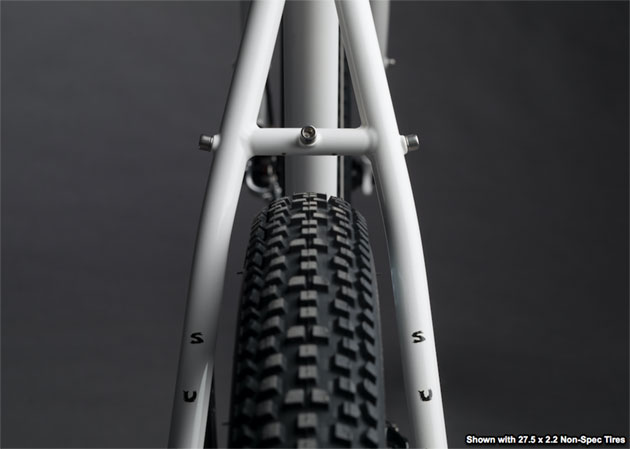 Zoomed in rear view of a the seat tube, seat stay and top of a tire, of a Surly Midnight Special bike, white