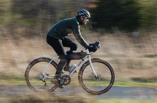 Right side view of a cyclist on a Surly Midnight Special bike speeding down a paved trail with tall brush shown behind