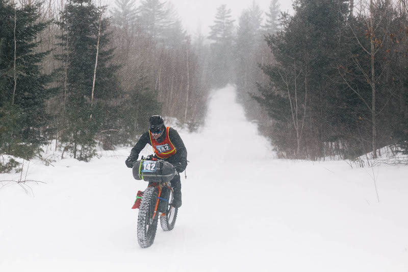 Front view of a cyclist riding a fat bike up a snow covered road hill in the forest on a snowy day