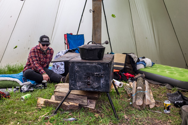 Person wearing a flannel shirt sitting on a sleeping bag next to a wood stove in a tent