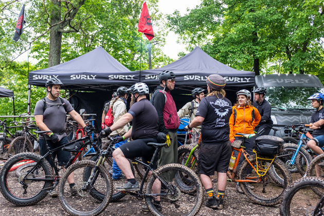 A group of cyclists with their bikes standing in front of two black Surly tents in the woods