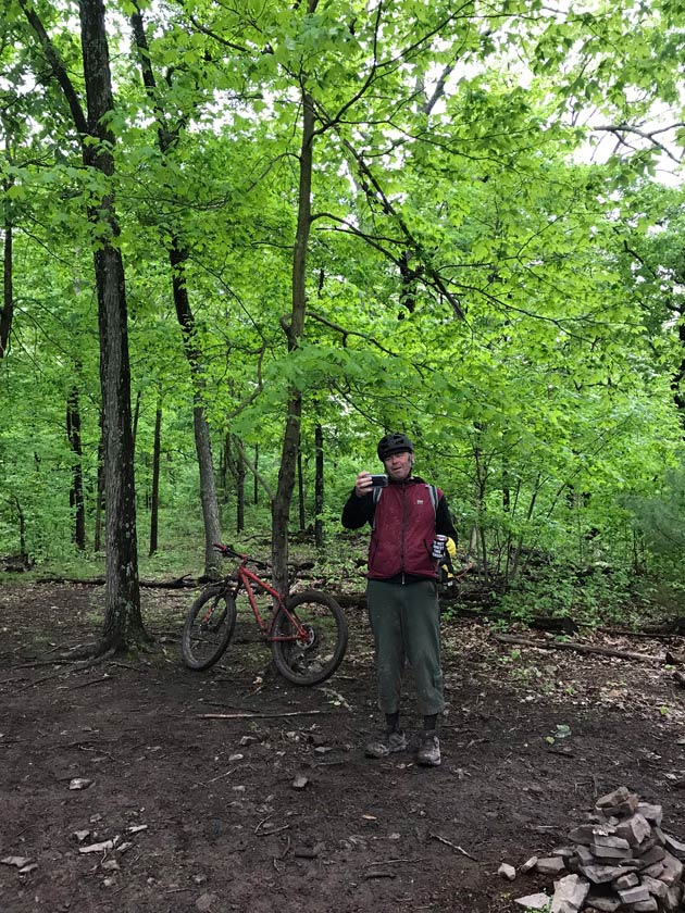 Cyclist standing on dirt with trees behind, holds up two cans