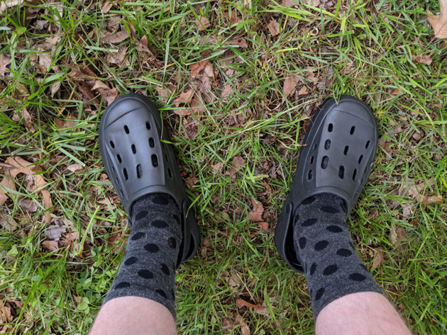Downward view of two legs wearing gear socks and Crocs standing in grass