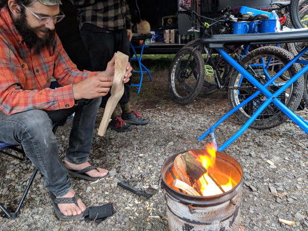 Person sitting in a camp chair holds kindling while looking at a fire in a steel bucket