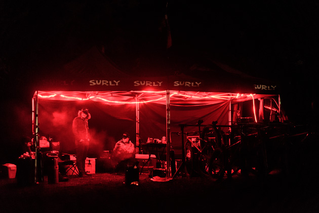 Two black Surly canopies with red string lights at night