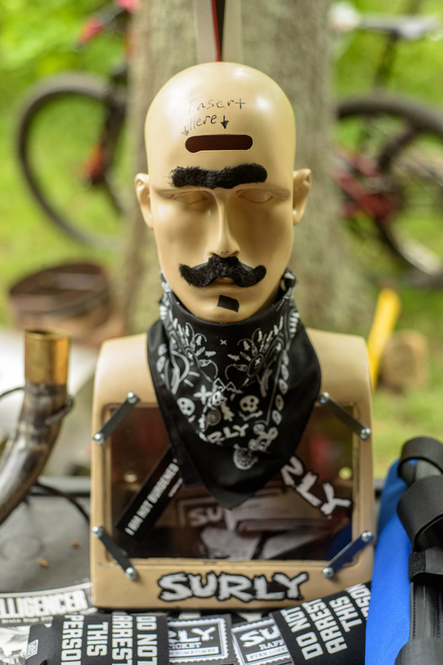 Chest up part of mannequin with a unibrow, mustache and black bandana around the next on a table with a Surly sticker