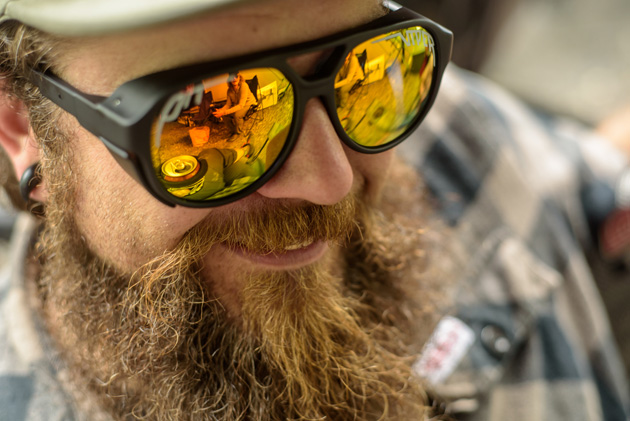 Person with a thick, red beard smiling wearing mirrored sunglasses