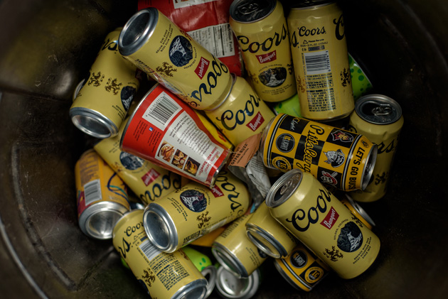 Downward view of a steel garbage can full of Coors beer cans