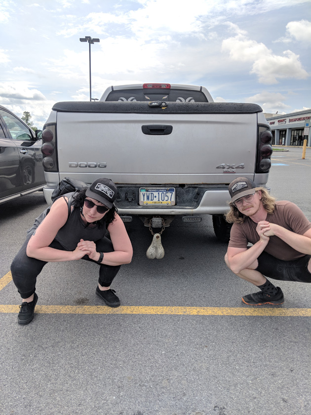 Two peoples dressed in Wayne's World attire squatting down a parking lot behind a truck