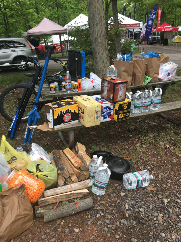 A picnic table with food and drink products in the woods with trees and canopies behind