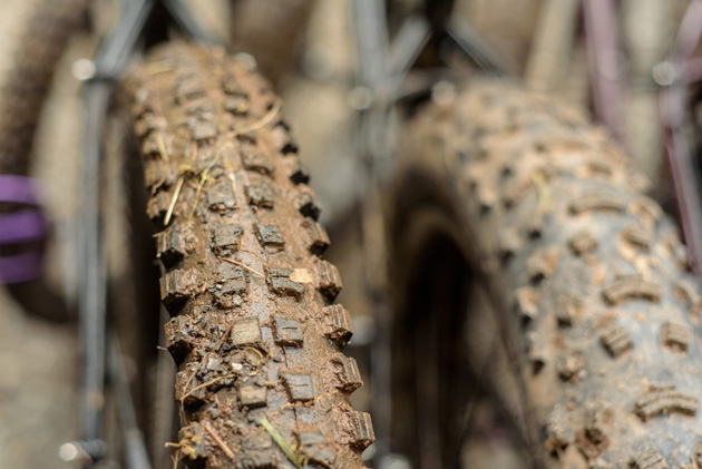 Close up front view of two knobby tire with mud in the tread