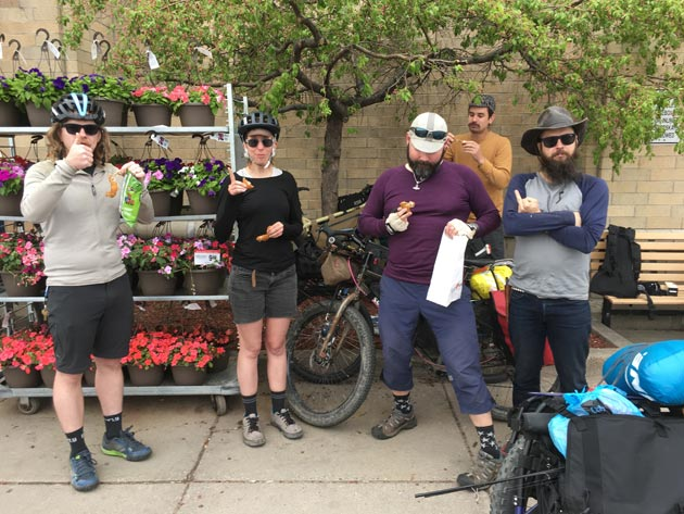 Cyclists standing with bikes on a sidewalk next to a rack of flowers, and a tree in front of a tan brick wall behind