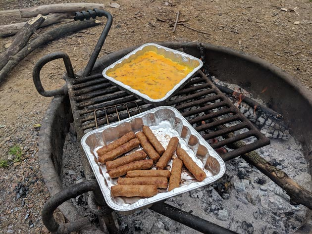 Downward view of a tray of sausage and a tray scrambled eggs on a cooking grate over a campfire ring