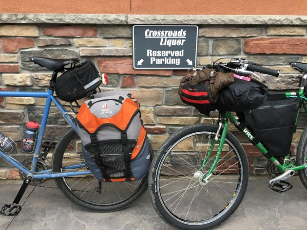 Left view of two Surly bikes leaning against a stone wall with a Crossroads Liquors Reserved parking side between