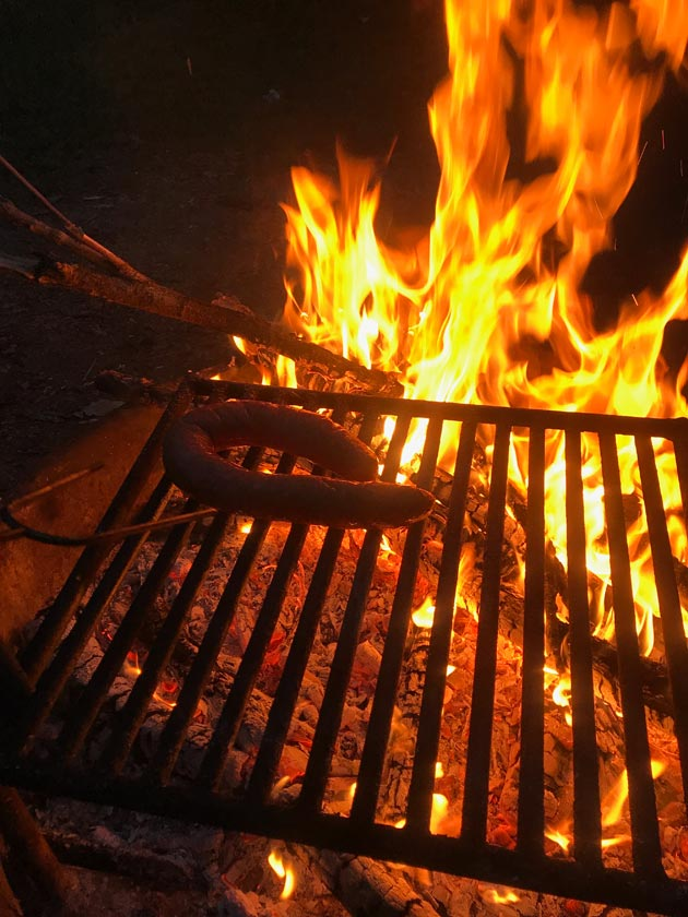 A ring sausage cooking on a grate above a campfire at night
