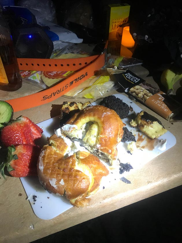 Downward view of a cutting board with a donut and strawberries, on top of a table with other various items