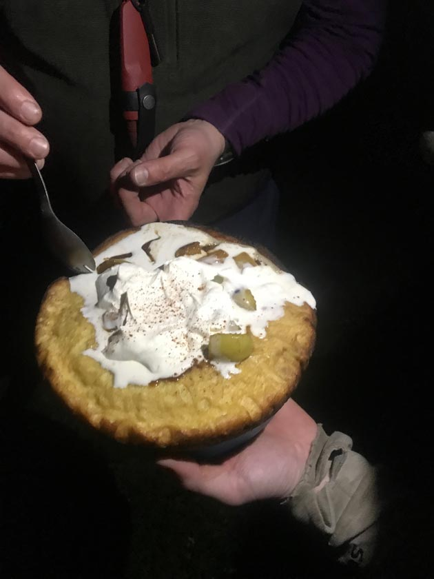 Downward view of a hand holding a large baked good with whipped cream while a person behind digs in with a spork