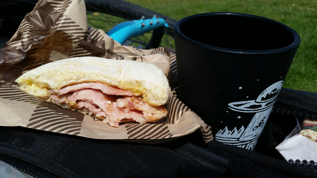 A black cup and a half eaten sandwich siting on a black bike bag
