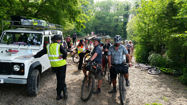 A group of cyclist with their bikes stand on a gravel lot in the trees next to a white SUV