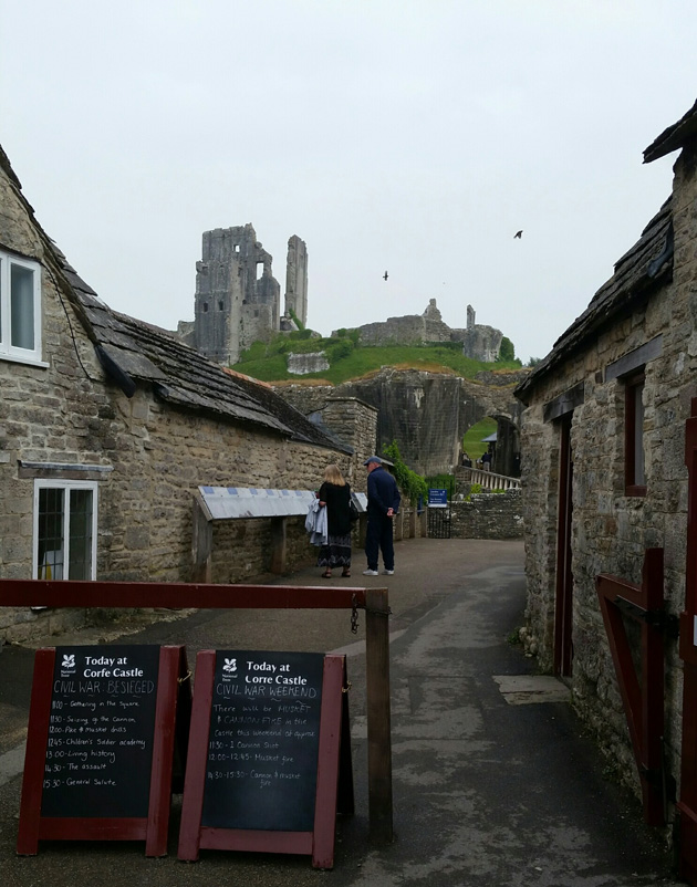Two persons walking on a narrow road between stone buildings with Corfe castle in the background up the hill
