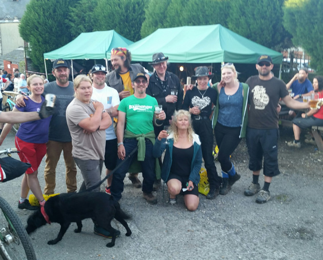 A group of people and a black dog looking ahead with people and a green canopies in the background