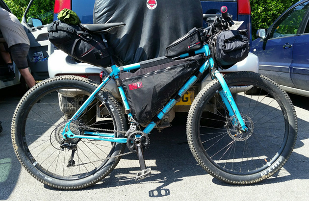 Right side profile  of a Surly bike, turquoise, with a front and seat pack behind a van