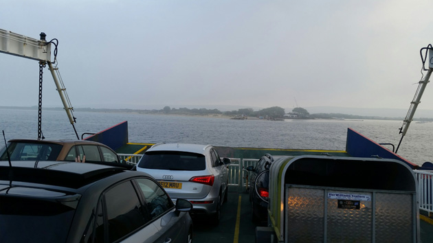 Front of a ferry with vehicles facing towards land on a cloudy day