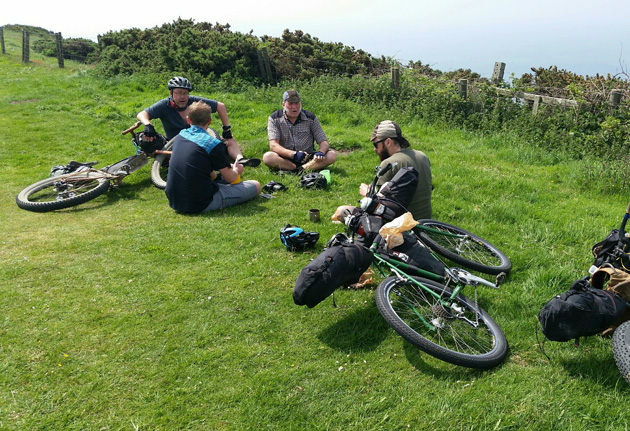 Four cyclist sitting on the grass with their bikes, loaded with gear, laying next to them