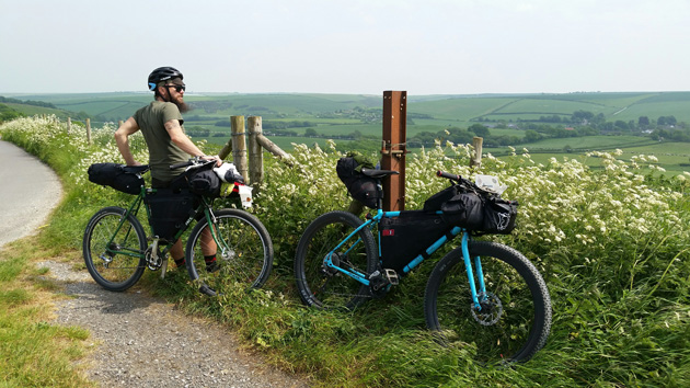 A cyclist in the grass on the side of the road standing with their bike, next to a bike with no rider leaning on a fence