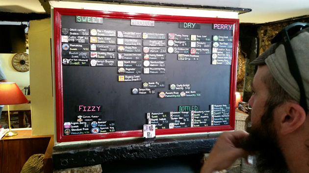 Person looking at a beer menu board with a red frame at an ordering counter