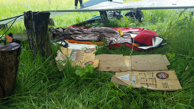 Boots and gear laying in the grass underneath an slightly elevated gray tarp