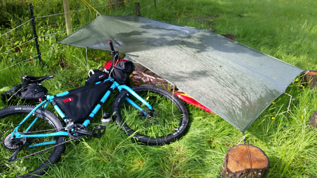 Surly bike, turquoise, loaded with gear, laying on the left side in the grass next to a gray tarp covering equipment