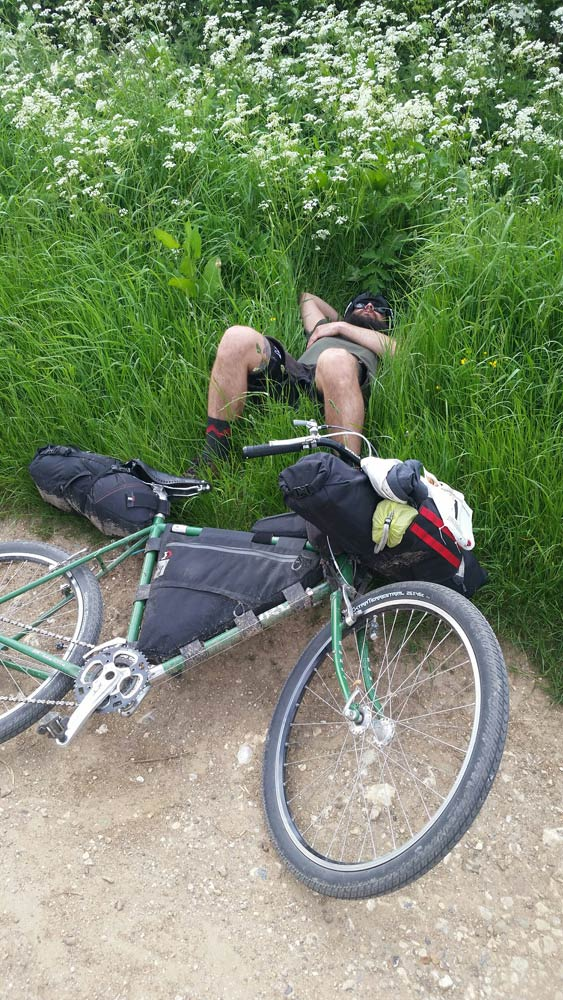 A cyclist laying down in tall, green grass and their green bike lying on it's left on top of gravel